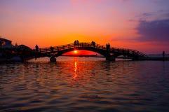 Gli amanti gettano un ponte su al tramonto Fotografie Stock