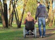 Gli amanti si accoppiano in sedia a rotelle e non handicappato Fotografia Stock