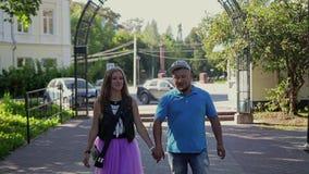 Gli amanti tipo e ragazza passano attraverso il parco che si tengono per mano e comunicano Una bella coppia nell'amore archivi video