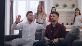 Gli amici allegri della società che giocano i video giochi si divertono e bevono la birra al fine settimana in appartamento moder archivi video