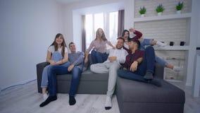 Gli amici allegri della società emozionale saltano sul sofà e si preparano per guardare la televisione nel partito luminoso della archivi video