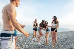 Gli amici ballano sulla spiaggia nell'ambito di luce solare del tramonto, divertiresi, felice, godono di fotografie stock libere da diritti