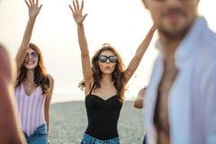 Gli amici ballano sulla spiaggia nell'ambito di luce solare del tramonto, divertiresi, felice, godono di fotografia stock libera da diritti