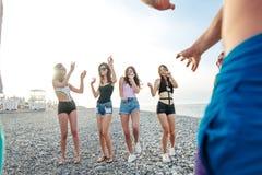 Gli amici ballano sulla spiaggia nell'ambito di luce solare del tramonto, divertiresi, felice, godono di immagini stock libere da diritti