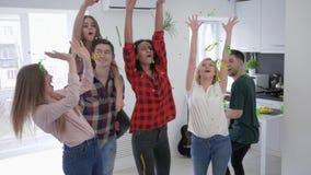 Gli amici che giocano con i coriandoli in cucina al rallentatore, la gioventù multirazziale sono ballanti e divertentesi ad un pa