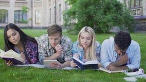 Gli amici che preparano per gli esami, materiali di lettura in università fanno il giardinaggio, istruzione video d archivio
