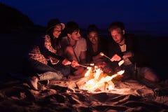 Gli amici che si siedono sui vetri del tintinnio della spiaggia si avvicinano al falò Fotografia Stock