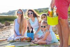 Gli amici che si siedono sulla sabbia alla spiaggia all'estate fanno un picnic Immagine Stock Libera da Diritti