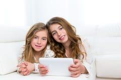 Gli amici dei bambini scherzano le ragazze che giocano insieme al pc della compressa Fotografia Stock Libera da Diritti