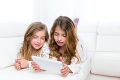 Gli amici dei bambini scherzano le ragazze che giocano insieme al pc della compressa Fotografia Stock