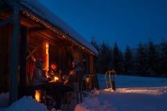 Gli amici del cottage dell'inverno di sera godono delle bevande calde Fotografia Stock Libera da Diritti