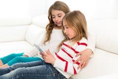 Gli amici della sorella dei bambini scherzano le ragazze che giocano insieme alla compressa p Fotografia Stock
