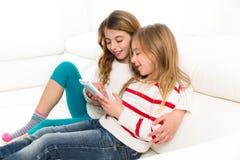Gli amici della sorella dei bambini scherzano le ragazze che giocano insieme alla compressa p Fotografie Stock Libere da Diritti