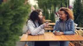 Gli amici di ragazze caucasici e afroamericani attraenti stanno bevendo il caffè e la seduta di chiacchierata in caffè all'aperto archivi video