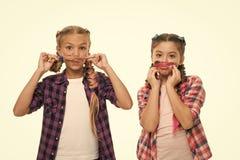 Gli amici di ragazze indossano le simili attrezzature hanno stessa acconciatura intreccia il fondo bianco Sorelle sguardo della f fotografia stock