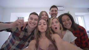 Gli amici di Selfie, smartphone grazioso della tenuta della ragazza e prende la foto con i fronti divertenti sul partito domestic