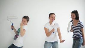Gli amici fa le riparazioni a casa Le ragazze divertenti ballano e dipingono le pareti nel piano video d archivio