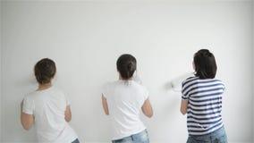 Gli amici fa le riparazioni a casa Le ragazze divertenti ballano e dipingono le pareti nel piano archivi video