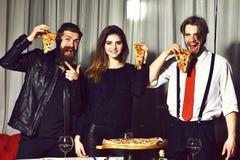 Gli amici felici che mangiano le fette saporite della pizza con i pollici aumentano i gesti Immagini Stock Libere da Diritti