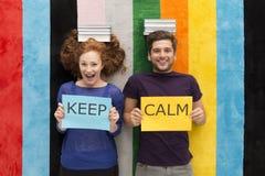 Gli amici felici con ` tengono il ` calmo per firmare dentro le mani Fotografia Stock