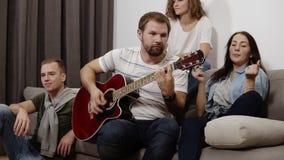 Gli amici felici si siedono intorno sul sofà ed ascoltano il canto del tipo e chitarra del gioco Riunisca per divertirsi con stock footage