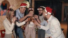 Gli amici felici stanno celebrando insieme il Natale, soffiando gli scoppi del partito stock footage