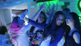 Gli amici femminili della società fa la foto ed il video dell'annotazione sull'androide in night-club alla moda video d archivio
