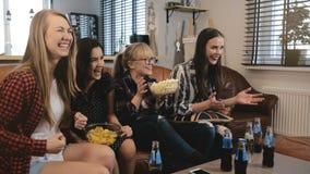 Gli amici femminili guardano la commedia filmare a casa sulla TV Le ragazze felici ridono insieme il movimento lento divertente d fotografie stock