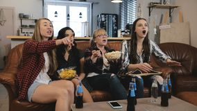Gli amici femminili guardano la manifestazione di TV con gli spuntini a casa Giovani ragazze europee che godono del movimento len fotografia stock