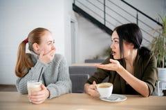 Gli amici femminili infelici discutono colpire le notizie Due giovani donne colpite che coprono bocca e che se esaminano il caffè fotografia stock libera da diritti