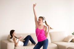 Gli amici femminili intrattiene con gli aggeggi digitali Immagini Stock