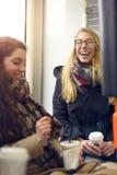 Gli amici femminili messi con caffè ridono insieme Fotografia Stock