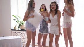 Gli amici femminili stanno imbrogliando intorno e divertimento che salta sul letto durante il partito nella stanza stock footage