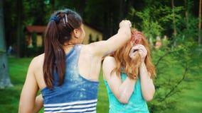 Gli amici gettano la polvere variopinta alla giovane donna dai capelli rossi al festival di Holi archivi video