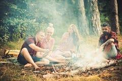 : Gli amici hanno picnic al falò negli uomini della foresta e le donne arrostiscono le salsiccie sopra immagini stock