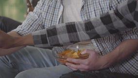 Gli amici hanno una birra bevente di resto e chip del cibo che si siedono sullo strato all'interno vicino su video d archivio