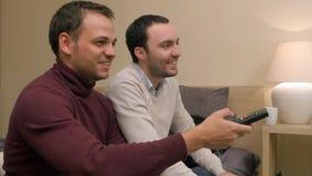 Gli amici maschii inseriscono e guardano la TV sedersi sul sofà a casa Fotografia Stock Libera da Diritti