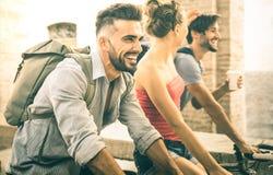 Gli amici multiculturali felici che si divertono la guida vanno in bicicletta nella vecchia città della città Immagine Stock