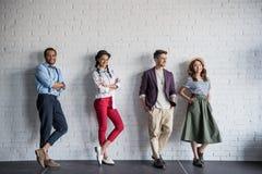 Gli amici multietnici che posano in vestiti alla moda si avvicinano al muro di mattoni fotografie stock