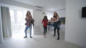 Gli amici multinazionali a casa fanno festa avendo corse di a due vie faccia a faccia in appartamento che gode delle feste in len