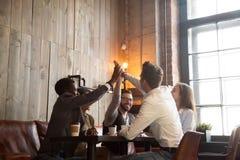 Gli amici multirazziali raggruppano dare il livello cinque che si siede alla tavola del caffè Immagine Stock Libera da Diritti