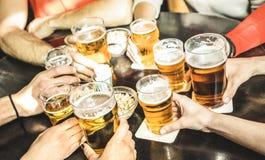 Gli amici passa la birra bevente al ristorante del pub della fabbrica di birra - Friendsh