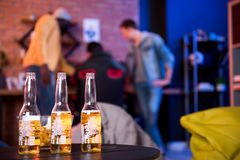Gli amici piacevoli stanno bevendo la birra inglese a casa Fotografia Stock
