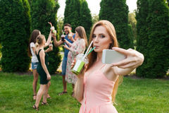 Gli amici riposano e bevono il succo nel giardino e la ragazza fa il selfie Fotografie Stock