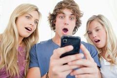Gli amici sono sorpresi al messaggio sul telefono Immagine Stock Libera da Diritti