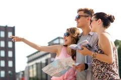 Gli amici sorridenti con la mappa e la città guidano all'aperto Fotografia Stock Libera da Diritti