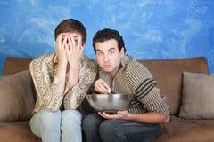 Gli amici spaventati mangiano il popcorn fotografia stock libera da diritti