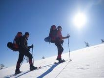 Gli amici stanno attraversando through le montagne Immagine Stock