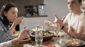 Gli amici stanno sedendo alla tavola nella casa e stanno godendo di dagli spaghetti fatti a mano con salsa e stanno chiacchierand archivi video