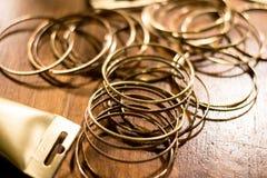 Gli anelli colorati dorati si sono sparsi dappertutto e una parte di un tubo Fotografia Stock
